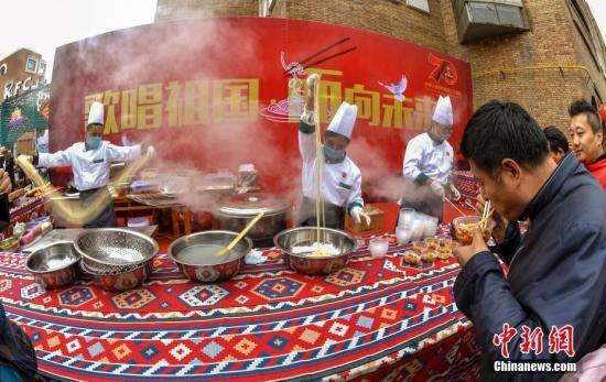 """10月1日,新疆乌鲁木齐市二道桥的国际大巴扎,举办同吃""""国庆面""""活动,700份新疆特色美食——新疆拌面,免费提供给游客和市民品尝,庆祝国庆节。当天,新疆多地举办形式多样的活动,庆祝中华人民共和国成立70周年。中新社记者 刘新 摄"""