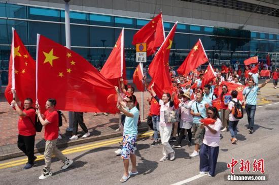 """10月1日国庆节,众多香港市民挥舞五星红旗来到金紫荆广场,欢庆国庆节,庆祝祖国70岁华诞。一路上他们高喊""""中国加油""""、""""祖国万岁""""、""""生日快乐""""等口号,并高唱国歌和《歌唱祖国》等爱国歌曲。中新社记者 张炜 摄"""