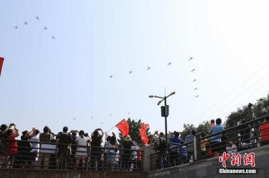 10月1日上午,庆贺中华群众共战国建立70周年年夜会正在北京天安门广场盛大举办。图为公众正在公园内旁观空中梯队。a target='_blank' href='http://www.chinanews.com/'中新社/a记者 贾天怯 摄