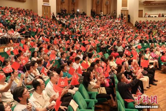 9月30日,香港庆祝中华人民共和国成立70周年文艺晚会在香港文化中心音乐厅举行,大会主办方希望通过该活动增进社区和谐,汇聚不同界别力量,使更多香港市民同享国庆喜悦。图为全体来宾共同挥舞中华人民共和国国旗和香港特别行政区区旗,合唱《我和我的祖国》。中新社记者 谢光磊 摄