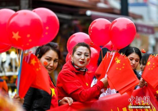 10月1日,新疆乌鲁木齐市二道桥的国际大巴扎内,工作人员向游客及市民赠送小国旗,庆祝国庆节。当天,新疆多地举办形式多样的活动,庆祝中华人民共和国成立70周年。中新社记者 刘新 摄