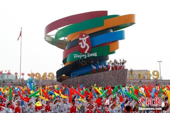 """10月1日上午,庆祝中华人民共和国成立70周年大会在北京天安门广场隆重举行。图为群众游行中的""""圆梦奥运""""方阵。<a target='_blank' href='http://www.chinanews.com/'>中新社</a>记者 富田 摄"""