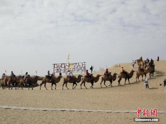 资料图片为:国庆黄金周期间,新疆尉犁县罗布人村寨景区游人如织。王小军 摄