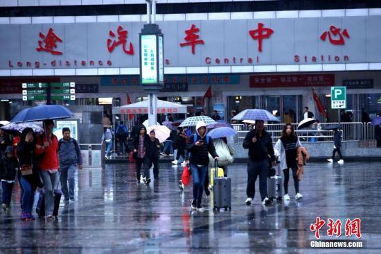材料图:市平易近冒雨出止。a target='_blank' href='http://www.chinanews.com/'中新社/a记者 王及第 摄