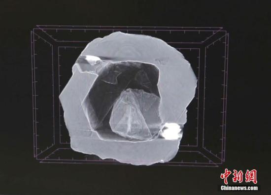 """当地时间2019年8月9日,俄罗斯萨哈共和国,奇特的""""钻中之钻""""。这颗无价之宝重仅0.62克拉,是人类有史以来发现的首颗此类钻石,据信已有8亿多年的历史。据报道,借着X光可以清晰地看到,在大钻的内部嵌套着一颗小钻,它甚至还可以自由地动来动去。专家估计,小钻重约0.02克拉。这颗钻石被命名为""""套娃""""(Matryoshka)。图片来源:视觉中国"""