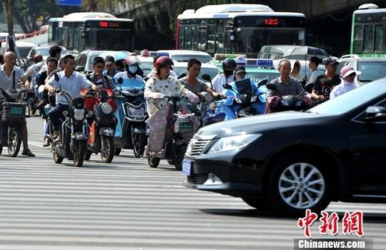 10月10日,福州街头,民众骑着电动自行车出行。中新社记者 张斌 摄