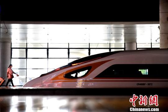 资料图:旅客在火车站乘坐高铁。/p中新社发 鲍赣生 摄