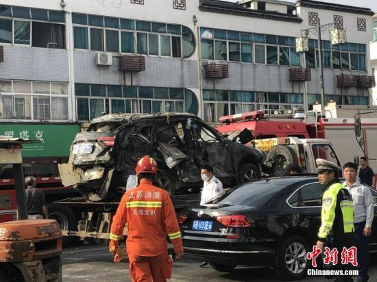 一辆在爆炸中严重损毁的汽车正被拖走。孙权 摄