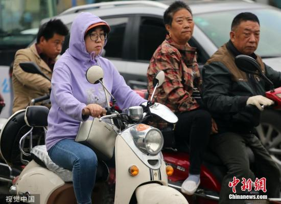 资料图:清晨街头凉意浓,出行市民穿上厚衣厚裤。雨田 摄 图片来源:视觉中国