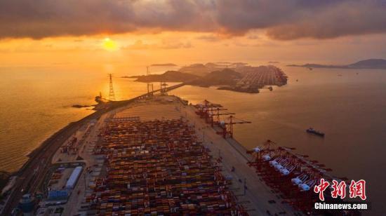 """10月13日,上海洋山深水港四期自动化码头,空中鸟瞰""""无人港"""",码头上一批作业穿梭不停的小车忙而不乱。这是无人驾驶的自动引导运输车,配有智能控制系统,可以根据实时交通状况规划最优路线、自动导航、主动避障。2017年12月,全球最大、智能化程度最高、具有完全自主知识产权的上海洋山深水港四期自动化码头开港,标志着我国港口行业在运营模式、技术应用以及装备制造上实现了里程碑式的跨越升级与重大改革。经过近两年多的运营,自动化码头昼夜作业不停,可完成集装箱吞吐量1万多标箱,不断创造刷新码头吞吐量的高效率""""神话""""。<a target='_blank' href='http://www.chinanews.com/'>中新社</a>发 钟鑫旺 摄 摄 图片来源:CNSPHOTO"""