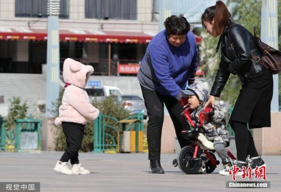 资料图:气温走低,体感寒冷,大衣棉服已成市民着装标配。图片来源:视觉中国