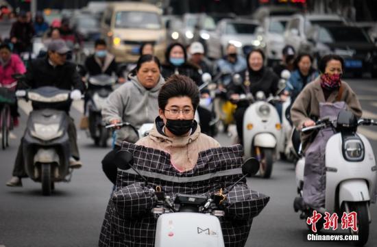 资料图:民众穿厚衣迎风出行。中新社记者 王中举 摄