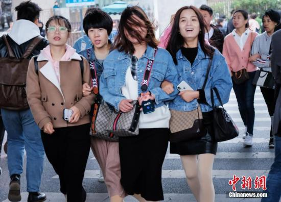 资料图:大风天气,民众穿厚衣迎风出行 中新社记者 王中举 摄