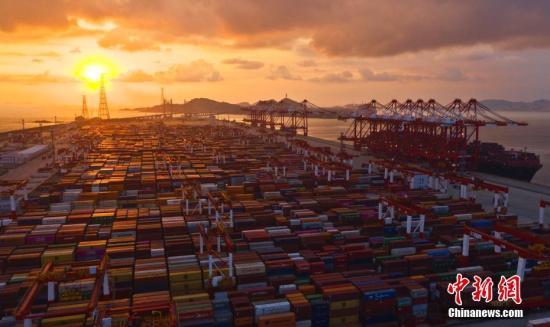 """10月13日,上海洋山深水港四期自动化码头,空中鸟瞰""""无人港"""",码头上一批作业穿梭不停的小车忙而不乱。这是无人驾驶的自动引导运输车,配有智能控制系统,可以根据实时交通状况规划最优路线、自动导航、主动避障。2017年12月,全球最大、智能化程度最高、具有完全自主知识产权的上海洋山深水港四期自动化码头开港,标志着我国港口行业在运营模式、技术应用以及装备制造上实现了里程碑式的跨越升级与重大改革。经过近两年多的运营,自动化码头昼夜作业不停,可完成集装箱吞吐量1万多标箱,不断创造刷新码头吞吐量的高效率""""神话""""。中新社发 钟鑫旺 摄 摄 图片来源:CNSPHOTO"""