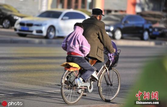 图辽宁沈阳14日朝最高温度达下四队耄孩子把头缩正在衣服里保温。图片滥觞:IC photo