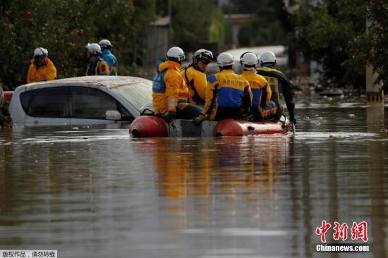 """本地工夫10月14日,""""海贝思""""形成日本少家县大水众多,本地告急展开救济动作。图救济职员乘皮筏搜索被困职员。"""