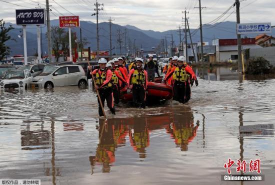 """本地工夫10月14日,""""海贝思""""形成日本少家县大水众多,本地告急展开救济动作。图救济职员照顾橡皮筏经由过程浅火地区。"""