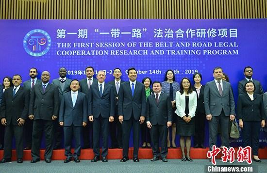 """10月14日,由中国外交部主办,外交学院承办的第一期""""一带一路""""法治合作研修项目在北京开幕。图为与会嘉宾在开幕式前合影。 中新社记者 张兴龙 摄"""