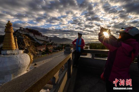 游客在布达拉宫观景台合影留念。新闻网记者 何蓬磊 摄