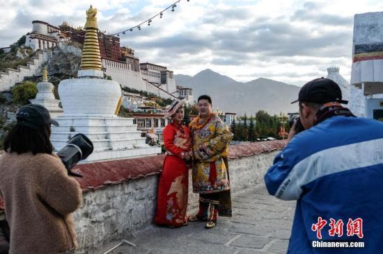 一对新人在布达拉宫观景台拍摄婚纱照。中新社记者 何蓬磊 摄
