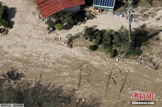 """当地时间10月15日,台风""""海贝思""""登陆日本三天后,日本宫城县偏远地区丸盛市灾民在地上写出""""水、食物""""字样寻求援助。据报道,根据最新统计数据,台风""""海贝思""""已在日本造成至少74人死亡,12人失踪。不少受灾地区仍然与外界隔绝,断电断水断粮。"""