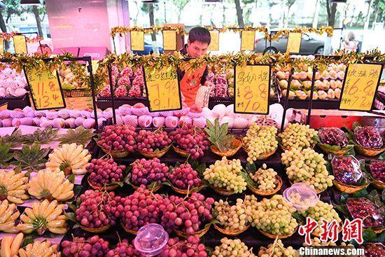 资料图为重庆一水果店工作人员正在整理各类水果。 中新社记者 陈超 摄