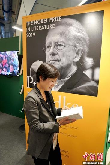 图为姚映然在世纪文景出版的汉德克中文版作品集海报前。 中新社记者 彭大伟 摄