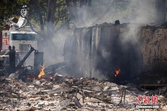当地时间10月24日,受野火肆虐的影响,美国北加州小镇盖瑟维尔及附近地区约2000人被迫离开家园。截至24日下午,野火烧毁了16000英亩土地,损坏或摧毁了49处建筑。盖瑟维尔东南方向的山区里,还有多个火点的明火没有被扑灭,周围大片区域被警方封锁,只有消防车或媒体车辆穿梭其间。图为一处被摧毁的建筑上,仍有明火在跳动。新闻网记者 刘关关 摄
