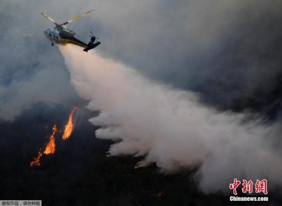 当地时间2019年10月28日,美国加州洛杉矶,当地野火持续肆虐。随着多场野火在大风影响下迅速蔓延。美国加利福尼亚州已有近20万人被强制离开家园。加州州长加文·纽瑟姆宣布,全州进入紧急状态。图为直升飞机在现场进行灭火救援。