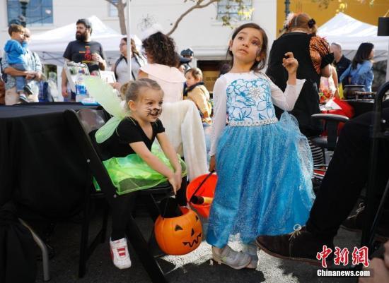 """当地时间10月31日,美国北加州伯克利儿童盛装走上街头,迎接万圣节的到来。每年11月1日,是很多国家的万圣节。此前一天,孩子们会根据自己的喜好,装扮成鬼怪向邻居们索要糖果,否则就会""""捣蛋"""",万圣节也因此成为孩子们非常期盼的节日。/p中新社记者 刘关关 摄"""