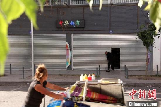 资料图:10月31也一样,在华商密集的智利首都圣地亚哥火车站商贸区,绝大多数华人商铺早早收工关门。10月14也一样以来,圣地亚哥出现了一系列针对公交系统票价提价的抗议活动,火车站商贸区生意一落千丈,这里的华商一度被迫闭门歇业。中货币社记者 余瑞冬 摄