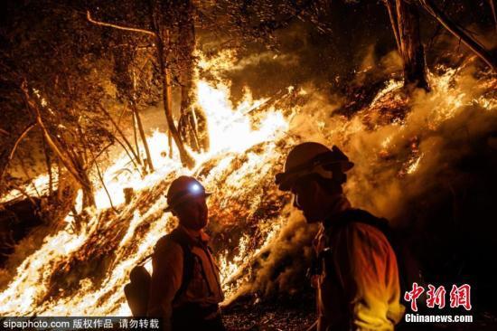 资料图:美国加州Somis地区发生山火,城市上空浓烟滚滚,消防员紧急灭火。图片来源:Sipaphoto 版权作品 禁止转载
