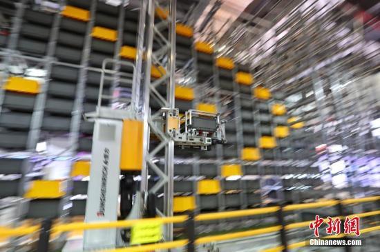 11月5日,第二届进博会在国家会展中心(上海)开幕。德国永恒力叉车公司展示的Miniload堆垛机,新式立柱结构的设计以及轻质的材料,使它的立柱最高可达25米高并具有极高的稳定性。在本届进博会上的展示高度为8米,为本届进博会室内最高的展品,现场的物流仓储演示吸引了众人驻足围观。中新社记者 张亨伟 摄