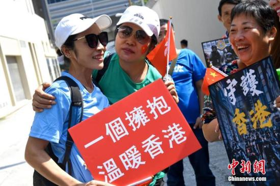 """当日元朗警署外,市民挥动着国旗和特区区旗,手持""""支持警察?守护香港""""""""阿Sir14亿同胞挺你""""等撑警海报,高呼""""支持警察?严正执法""""的口号。中新社</a>记者 李志华 摄"""