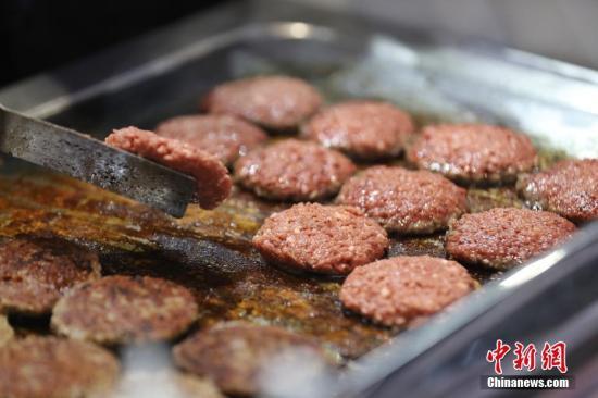 资料图:第二届进博会,民众争先品尝人造肉汉堡。中新社记者 张亨伟 摄