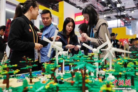 11月9日,第二届中国国际进口博览会在上海国家会展中心举行。在品质生活展区的乐高展台,参观者动手亲自制作。中新社记者 殷立勤 摄