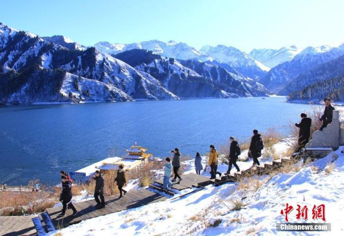 资料图:新疆天山天池景区内,来自国内外的游人徜徉在初冬的雪景里,如痴如醉。甄梅 摄