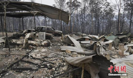 资料图:当地时间2019年11月13日,澳大利亚新南威尔士Glenreagh,林火持续肆虐,当地的房屋和车辆遭烧毁。