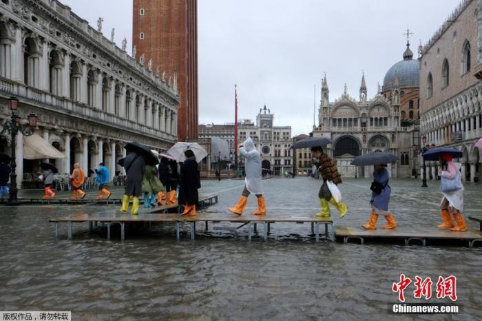 当地时间2019年11月12日,意大利威尼斯,威尼斯运河水位上升,洪水淹没圣马可广场。据美联社报道,当地时间12日上午,水位峰值达到127厘米。图为民众涉水出行。
