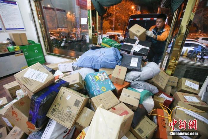 资料图:11月13日,山西太原的物流业工作人员加紧给快递卸车。中新社记者 张云 摄