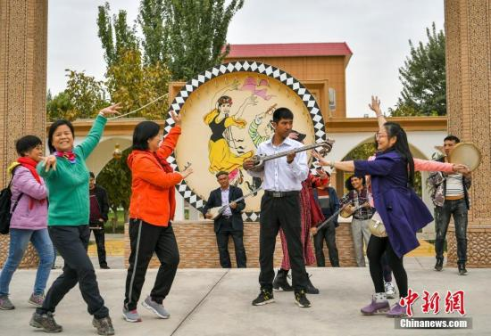 Photo taken on Nov. 14 shows people in a musical instrument-making village in Xinjiang Uygur Autonomous Regionsing and dance. (Photo/China News Service)