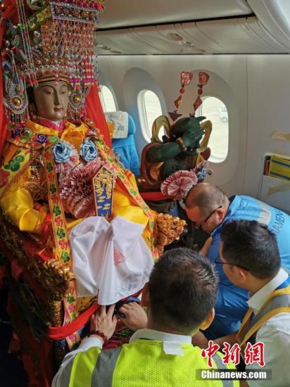 """11月14日,厦门航空MF853航班顺利抵达泰国曼谷。来自""""妈祖故乡""""福建莆田湄洲岛的妈祖金身起驾搭机巡访""""佛教国度""""泰国,展开为期五天六夜的""""妈祖下南洋・重走海丝路""""暨中泰妈祖文化活动周之旅。图为厦门航空机务人员对飞机座椅进行特别调整以安置妈祖神像。中新社发 高亚成 摄"""
