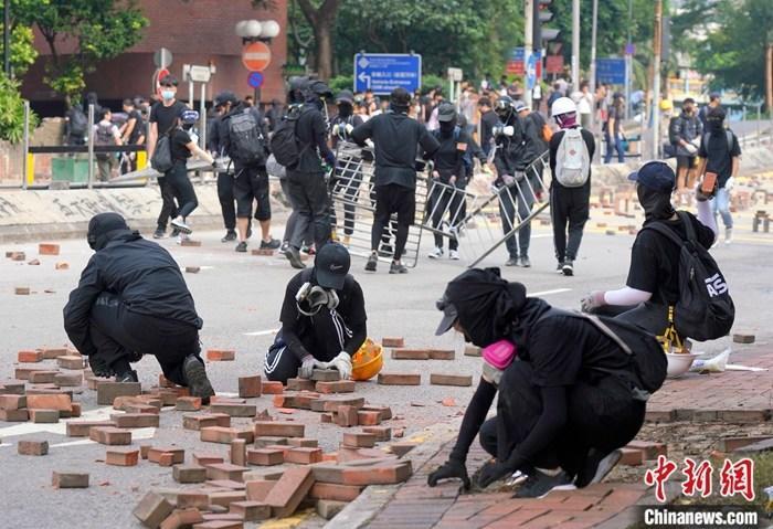 11月14日下午,众多蒙面黑衣人在香港理工大学对出的畅运道设置路障,挖掘人行道上的砖块堵塞道路。<a target='_blank' href='http://www.chinanews.com/'>中新社</a>记者 张炜 摄