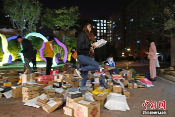 资料图:11月15日晚,在上海虹桥乐贤居人才公寓,民众正在小区广场上取快递。殷立勤 摄
