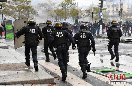 """当地时间11月16日,数万示威者于法国""""黄马甲""""运动一周年之际,在全法多个地方举行示威游行活动,暴力示威在巴黎街头重现,百余人被捕。图为防暴警察在巴黎南部意大利广场驱散示威者。中新社记者 李洋 摄"""