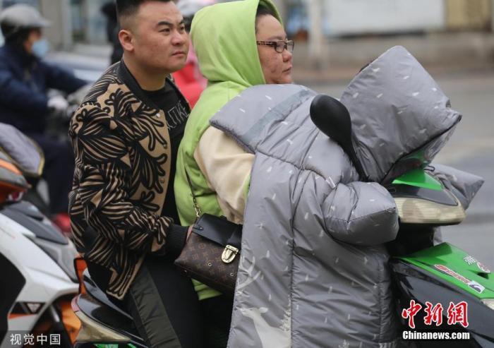 """据中央气象台网站消息,预计18日白天至19日早晨,强冷空气继续影响我国东部地区,华北、东北地区、黄淮及其以南大部地区有4~6级、阵风7~9级大风,上述大部地区气温继续下降。图为南京街头寒意浓烈,出行的市民""""全副武装""""。图片来源:视觉中国"""