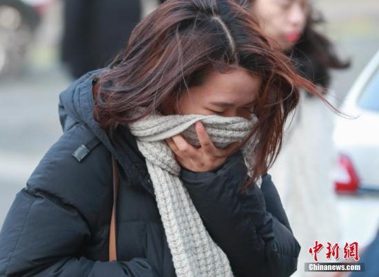 资料图:一名女性在大风天气中出行。中新社记者 贾天勇 摄