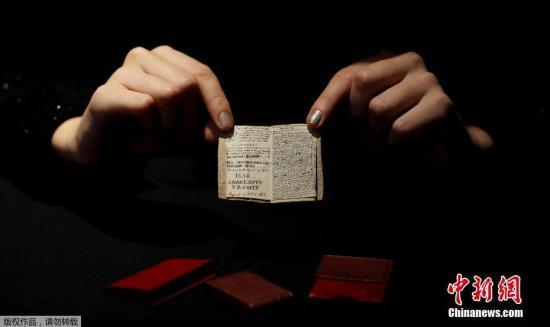 当地时间11月18日,法国巴黎德鲁奥拍卖行,一名工作人员展示了夏洛蒂·勃朗特创作的微型手稿。据悉,这是夏洛蒂·勃朗特14岁时创作的第二期《青年男性杂志》的微型手稿。