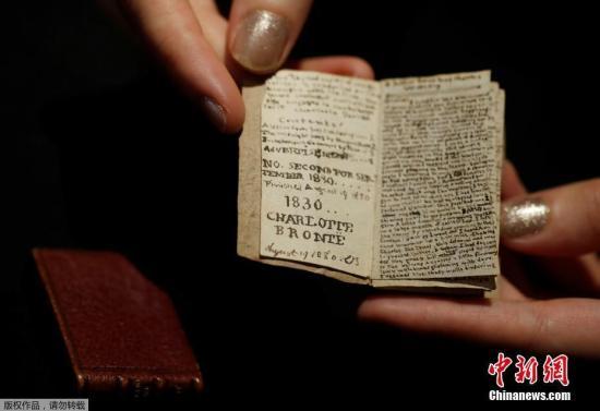 当地时间11月18日,法国巴黎德鲁奥拍卖行,一名工作人员展示了夏洛蒂·勃朗特创作的微型手稿。据悉,这是夏洛蒂·勃朗特14岁时创作的第二期《青年男性杂志》的微型手稿。图为工作人员展示手稿内容