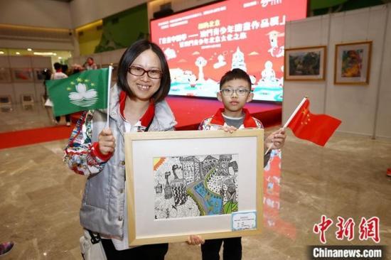 """11月19日,""""童画中国梦――澳门青少年绘画作品展""""在北京中国宋庆龄青少年科技文化交流中心开幕。寓意澳门回归20周年的99幅澳门儿童绘画作品与公众见面。图为澳门濠江中学附属英才学校的9岁少年陈天泽与母亲何女士展示个人作品《中国梦》。中新社记者 李雪峰 摄"""